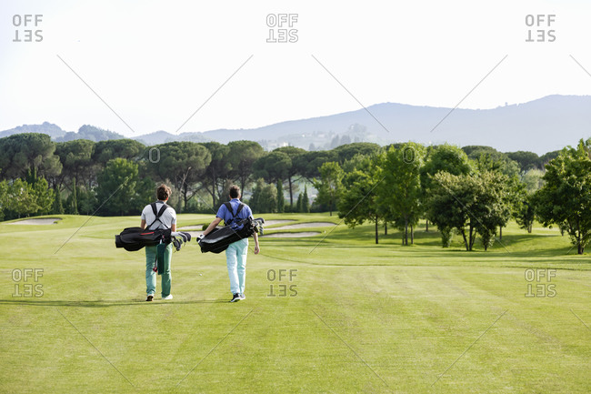 Friends carrying golf bag walking on golf course