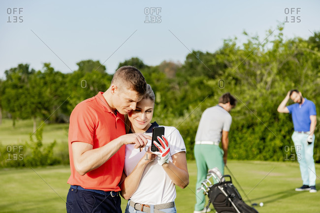 Couple using smartphone on golf course, friends playing golf in background