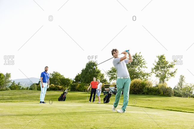 Friends playing golf on golf course