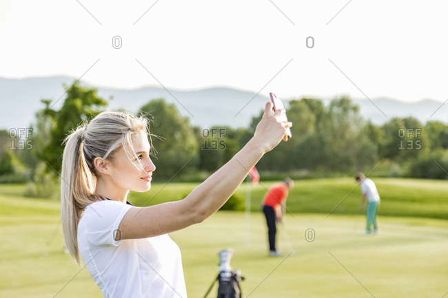Woman taking selfie on golf course, friends playing golf in background