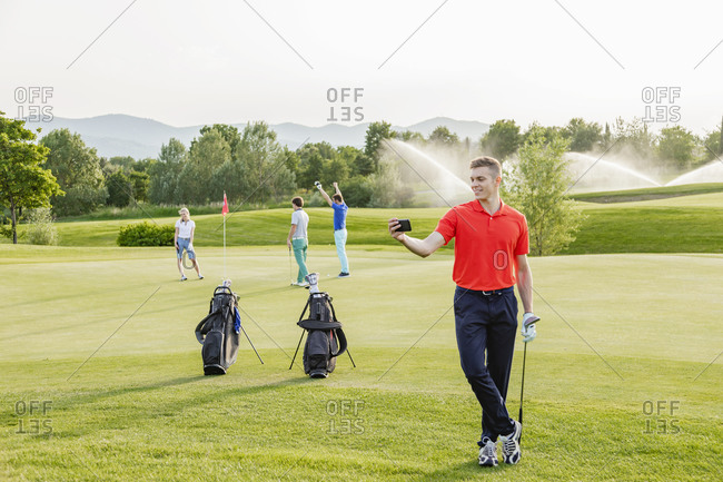 Man taking selfie on golf course, friends playing golf in background