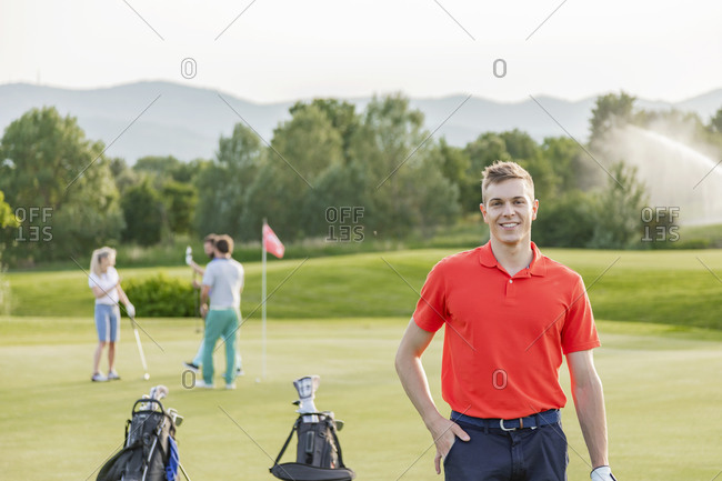 Man with friends playing golf on golf course in background