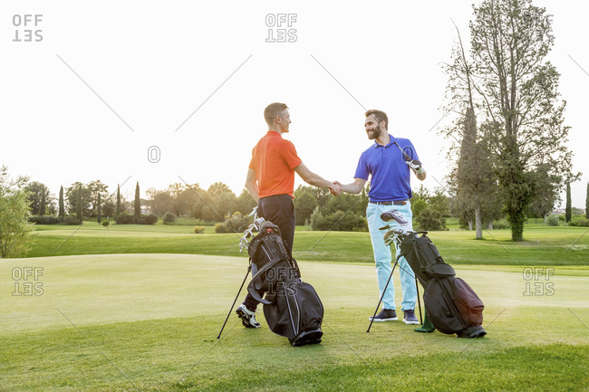 Friends shaking hands on golf course