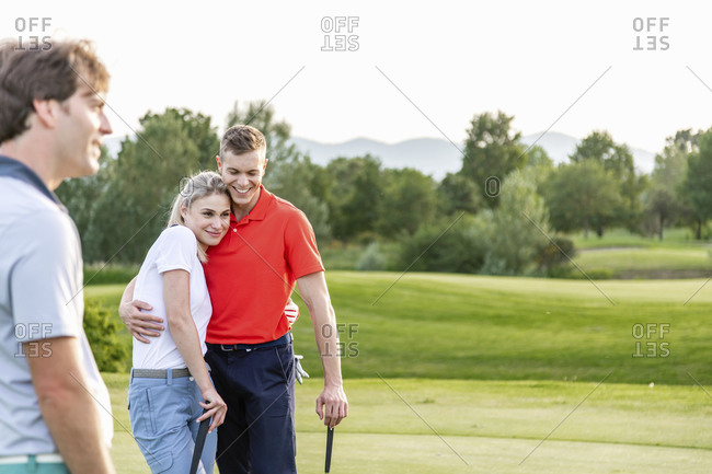 Man with couple hugging on golf course