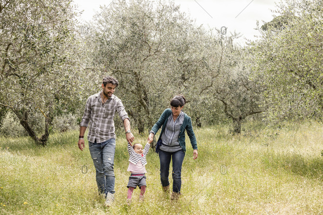 Couple running with toddler girl in garden, Florence, Italy