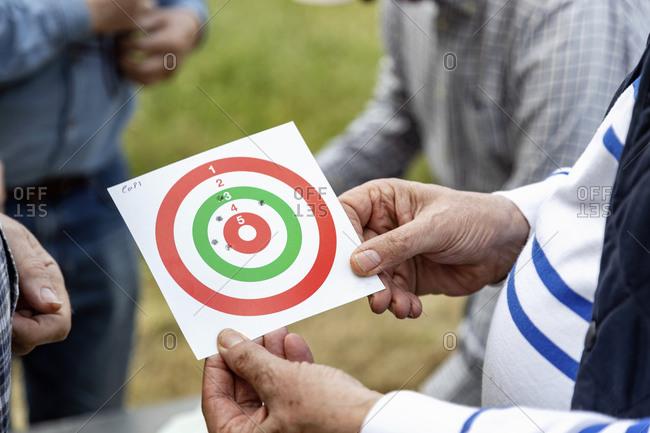 Men looking at bulls eye at rifle target shooting, Florence, Italy