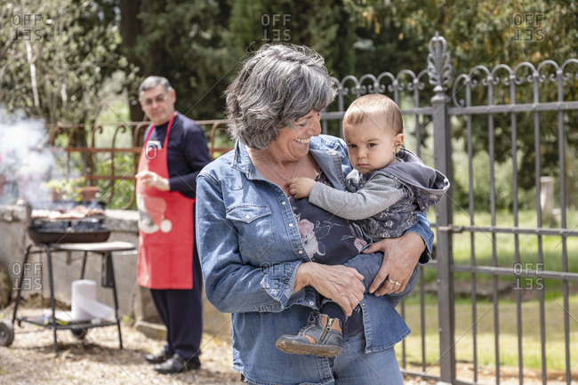 Grandmother carrying baby boy at family BBQ gathering, Florence, Italy