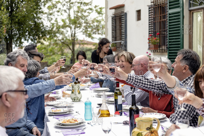 Family toasting at outdoor lunch in garden, Florence, Italy