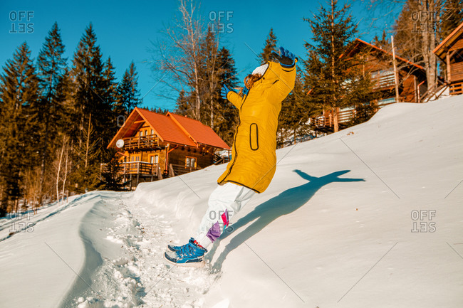 Young woman leaping backwards into deep snow near a chalet.