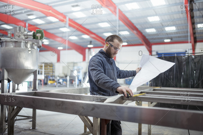 Engineer inspecting plans in metal fabrication factory.