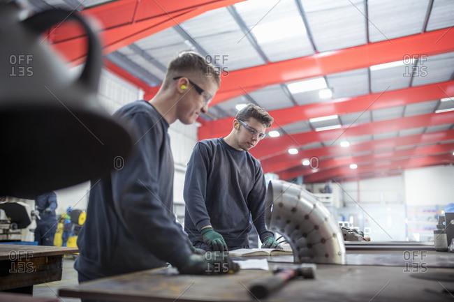 Apprentice engineers inspecting pipe bend in metal fabrication factory.