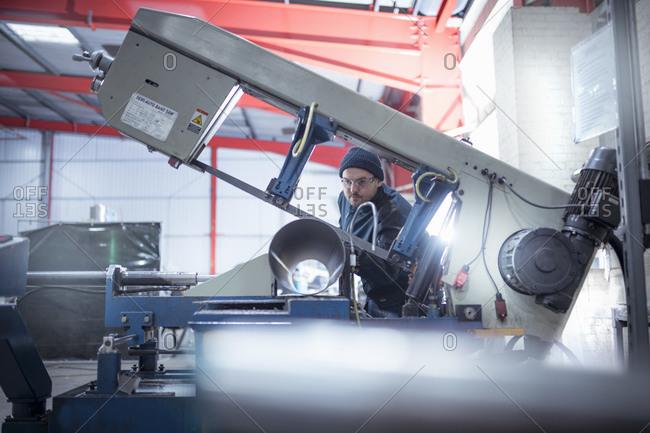 Engineer sawing pipe in metal fabrication factory.