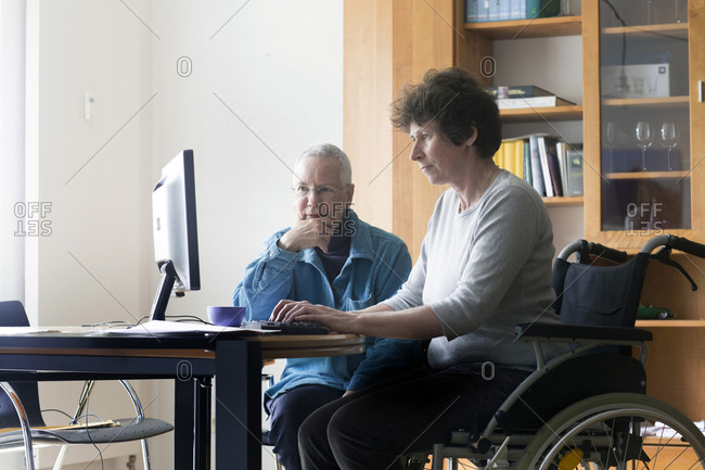 Senior woman and woman in a wheelchair sitting at a table, working on computer.