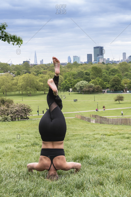 Rear view of young woman in a headstand on a meadow, doing yoga.