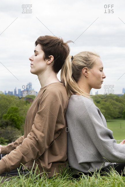 Two young women sitting back to back on a meadow, eyes closed.