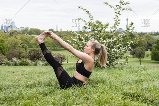 Young woman sitting on meadow in boat pose, doing yoga.