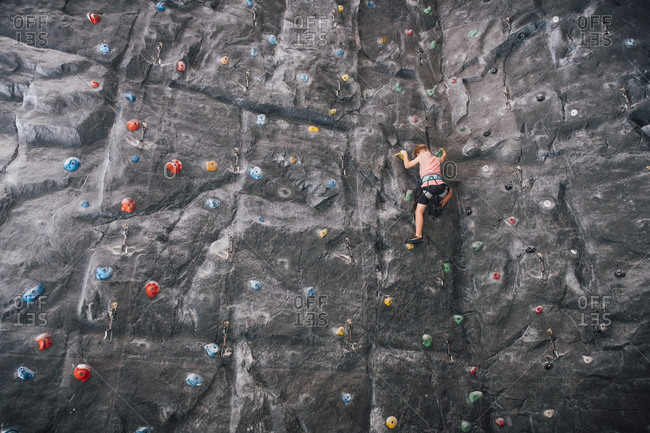Low angle view of young boy ascending rock climbing wall in Bolzano, Lombardy, Italy.