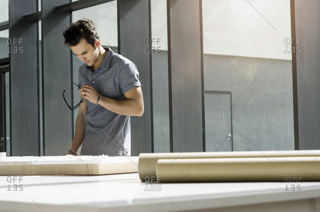 Young male architect standing at a table, working on an architectural model.