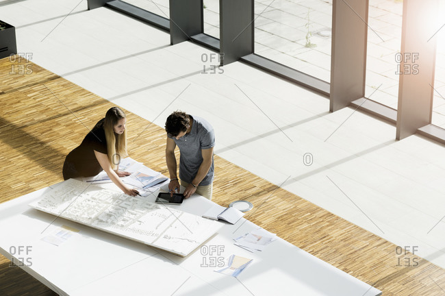 High angle view of two young architects working on an architectural model.