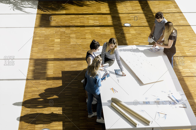 High angle view of group of young architects working on an architectural model.