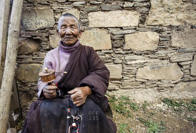 A Tibetan woman deeply focused in her prayers in her village in the Tibetan Plateau