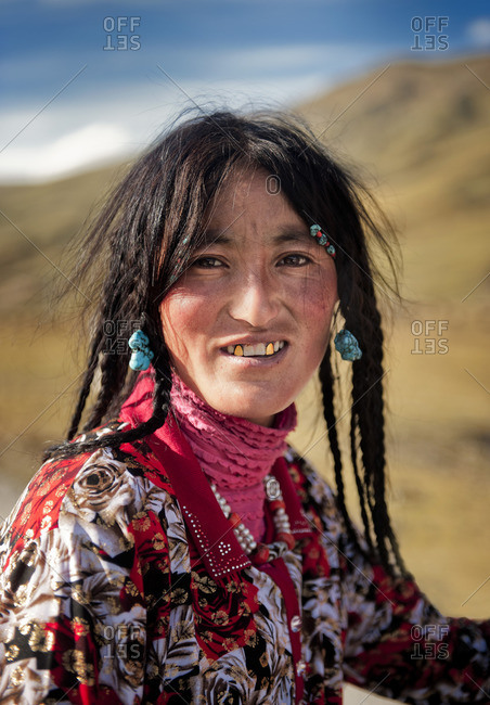 A young Tibetan woman wears traditional jewelry typical of her ethnic group