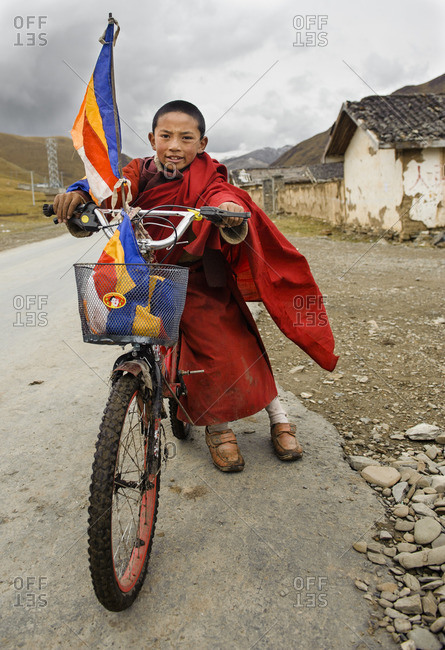 January 1, 1970: A young Tibetan Buddhist monk with his bicycle near his monastery, Tibetan Plateau