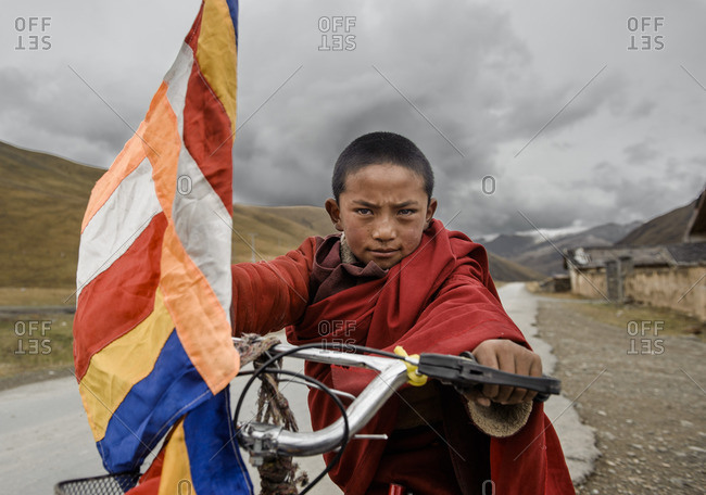 A young Tibetan Buddhist monk with his bicycle near his monastery, Tibetan Plateau