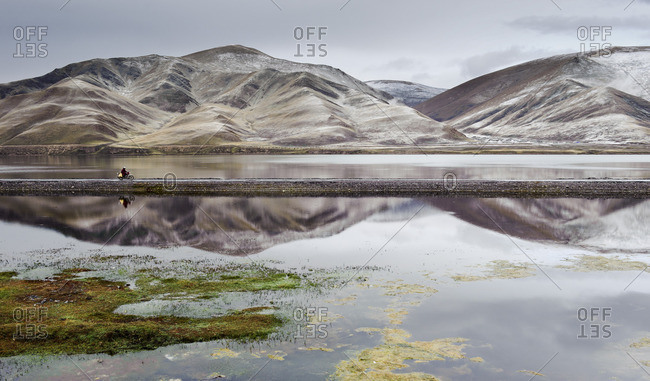 Tibetan monk drives past a reservoir near Sershul, Kham, Tibet after a snowstorm on a motorcycle
