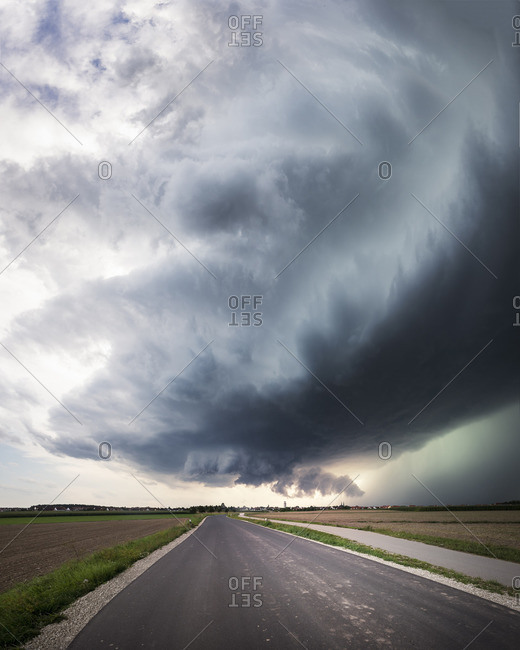 Panorama of a super cell with a low-lying wall cloud, an upwind base and a glowing green precipitation core over a country road near Heilsbronn, Bavaria, Germany