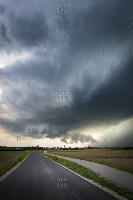 Low-hanging wall cloud, updraft base and heavy precipitation core of a classic supercell over a country road near Heilsbronn, Bavaria, Germany