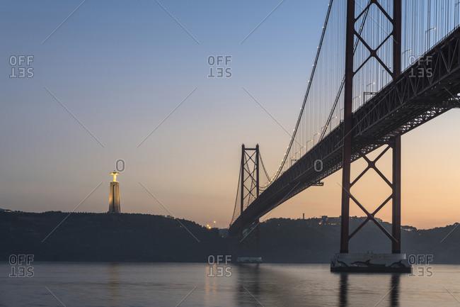 January 1, 1970: Ponte 25 de Abril in Lisbon, Cristo Rei statue, sunset, Portugal