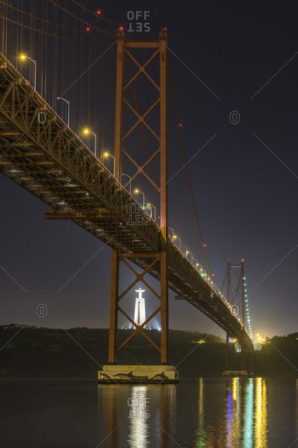 January 1, 1970: Night shot of Ponte 25 de Abril (bridge) and Cristo Rei (Christ statue in Almada), Lisbon, Portugal