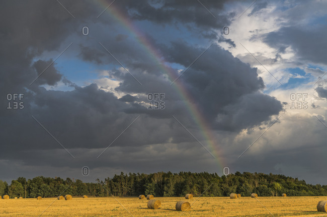 Thunderstorm with rainbow over stubble field, Thuringia, Germany