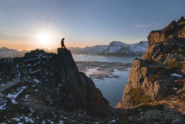 Hiker at Hoven in the back light looks into the abyss and onto the surrounding landscape, Hoven, Lofoten, Nordland, Norway