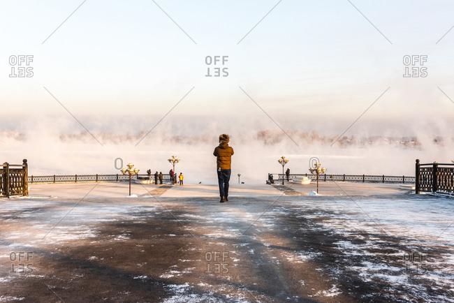 Man standing on the banks of the Irkut, Irkutsk, Siberia, Russia