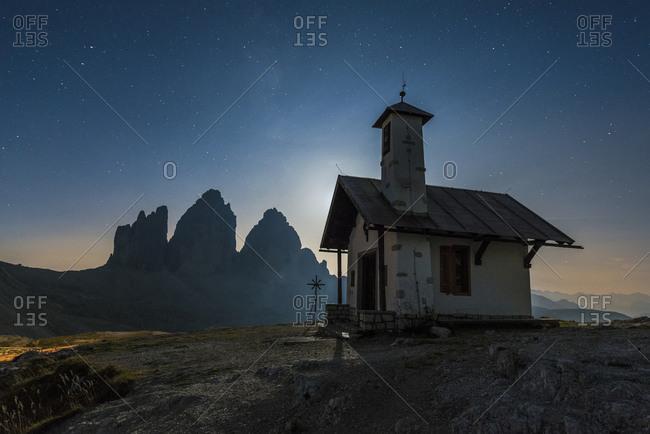 Tre Cime di Lavaredo with chapel at night, Tre Cime Natural Park, Dolomites, South Tyrol, Italy