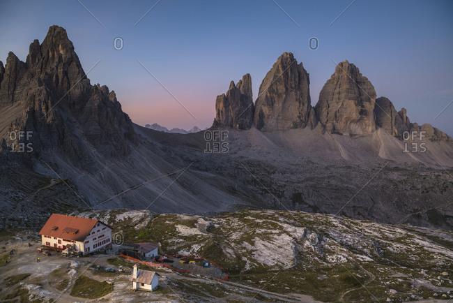 August 31, 2017: Tre Cime di Lavaredo and Triassic Hut at sunrise, Tre Cime Natural Park, Dolomites, South Tyrol, Italy
