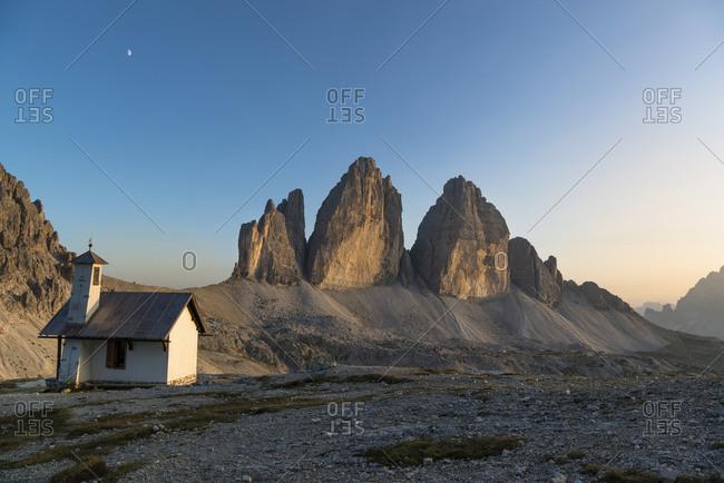 Tre Cime di Lavaredo with chapel at sunset, Tre Cime Natural Park, Dolomites, South Tyrol, Italy