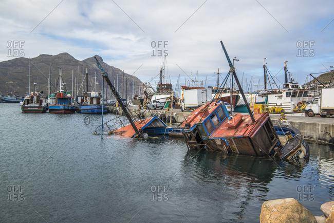 March 5, 2017: Sunken fishing boat in the harbor of Kalk Bay, False Bay, South Africa