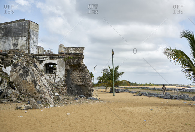 Keta, Ghana - November 7, 2019: Woman walking on the beach nearby the remains and ruins of the Fort Prinzenstein