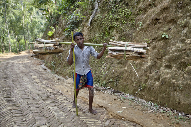 Nirala Para village, Sreemangal, Bangladesh - April 30, 2013: A man in the Khasi tribe carrying wood uphill