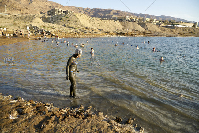 Dead Sea, Jordan - October 24 2017: Woman covered by mud and people bathing in the Dead Sea