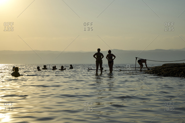 Dead Sea, Jordan - October 24 2017: Silhouettes of people covered with mud and bathing in Dead Sea at sunset