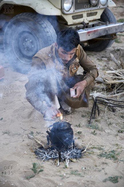 Wadi Rum, Jordan - March 21, 2019: Young Bedouin man preparing tea in Wadi Rum desert at sunset