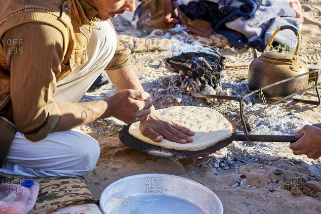 Wadi Rum, Jordan - March 22, 2019: Bedouin man preparing local bread in Wadi Rum desert in Jordan