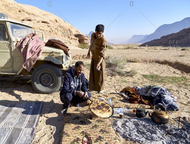 Wadi Rum, Jordan - March 22, 2019: Two Bedouin men preparing local bread in Wadi Rum desert in Jordan