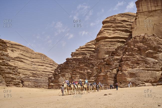 Wadi Rum, Jordan - March 23, 2018: Tourists riding camels among the majestic rocks of Wadi Rum desert