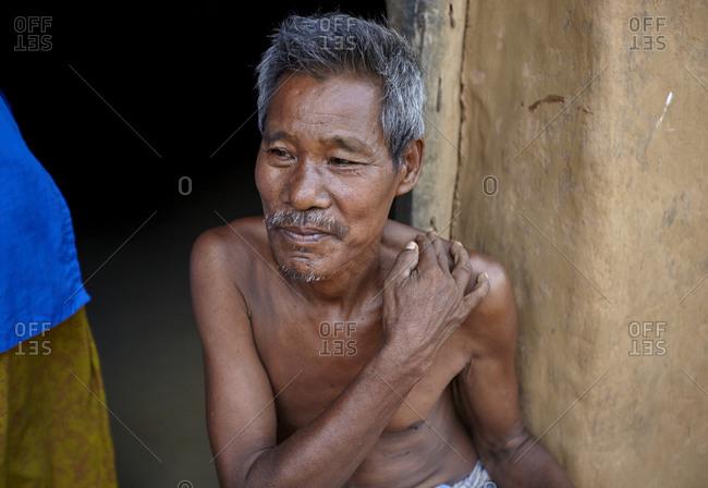 Garo Line Para Village, Sreemangal, Bangladesh - May 2, 2013: Portrait of a Garo tribal man sitting by doorway
