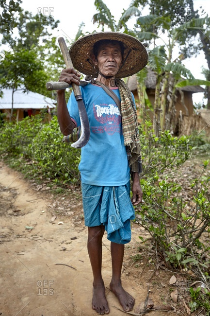 Garo Line Para Village, Sreemangal, Bangladesh - May 2, 2013: Portrait of a Garo tribal man holding farming tools